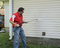 Contractor Using A Pressure Washer To Clean Vinyl Siding Stock Photo