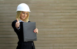 Contractor woman. Engineer or contractor woman with safety hat and leather folder showing the ok sign in front of a brick wall Royalty Free Stock Photography