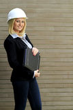 Contractor woman. Engineer or contractor woman with safety hat and leather folder showing the ok sign in front of a brick wall royalty free stock photo