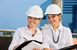 Contractors. Female contractors in a front of building site (focus on blonde royalty free stock image