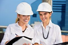 Contractors. Female contractors in a front of building site (focus on blonde royalty free stock photo
