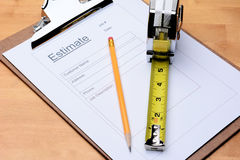 Contractors Estimate Form. Closeup of a Contractors estimate form with a pencil and tape measure on a wooden table. Horizontal format filling the frame royalty free stock image