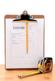 Contractors Estimate Form Vertical. Closeup of a Contractors estimate form with a pencil and tape measure on a wooden table. Vertical witha white background stock image