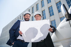 Contractors in formal wear looking at blueprint while standing near bus. Outdoors stock images