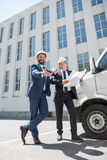 Contractors in formal wear looking at camera while standing near bus outdoors. Smiling contractors in formal wear looking at camera while standing near bus stock photos