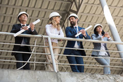 Contractors in formal wear talking while standing at construction site. Team of contractors in formal wear talking while standing at construction site royalty free stock photo