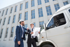 Contractors in formal wear talking while standing near bus. Outdoors royalty free stock photo