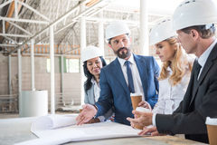 Contractors in formal wear talking while working with blueprints at construction. Group of contractors in formal wear talking while working with blueprints at Royalty Free Stock Photos