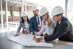 Contractors in formal wear working with blueprints at construction area. Group of contractors in formal wear working with blueprints at construction area stock photo