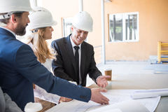 Contractors in formal wear working with blueprints at construction. Mature contractors in formal wear working with blueprints at construction royalty free stock photos