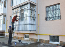 Contractors install window iron security bars. KIEV, UKRAINE - FEBRUARY, 5, 2016: Contractors install window iron security bars Stock Photography