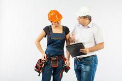 Contractors people discussing the plan of building over white background. Foreman with builder women wearing helmets stock photo