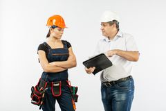 Contractors people discussing the plan of building over white background. Foreman with builder women wearing helmets stock image