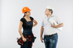 Contractors people discussing the plan of building over white background. Foreman with builder women wearing helmets royalty free stock photo