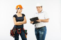 Contractors people discussing the plan of building over white background. Foreman with builder women wearing helmets stock photos