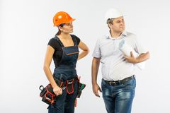 Contractors people discussing the plan of building over white background. Foreman with builder women wearing helmets royalty free stock photos