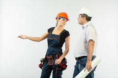 Contractors people discussing the plan of building over white background. Foreman with builder women wearing helmets stock images