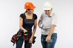 Contractors people discussing the plan of building over white background. Foreman with builder women wearing helmets stock photography