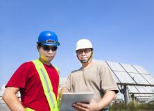 Contractors and standing before solar panels Stock Images