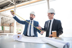 Contractors talking while working with blueprints at construction. Mature contractors talking while working with blueprints at construction stock photo