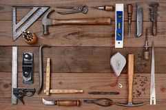 Contractors Tools. High angle shot of an assortment of contractors well used tools. Horizontal format on a rustic wood background, with a bland space in the Stock Image
