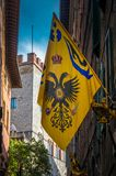 Contrade Aquila - Eagle flag hanging on the narrows streets in the old city center of Siena stock photo