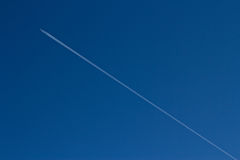 Contrail of an airplane and a blue sky Royalty Free Stock Image