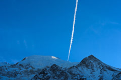 Contrail of an airplane over a snowy mountain Royalty Free Stock Image