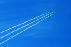 Contrail arrow. Three military jet planes with contrail in the clear blue sky stock images