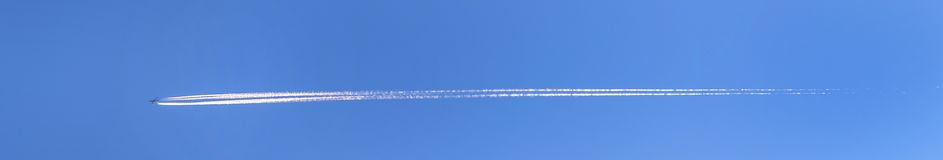 Contrail in a blue  sky. Contrail in a blue and orange sky stock photography