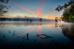 Contrail Colors and Reflection - Cross in the sky. Contrail Colors and Reflection - Crosses in the sky, trees and Water - Autumn sunrise in Arkansas stock images