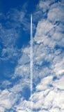 Contrail d'avion à réaction par des nuages en ciel bleu Images libres de droits