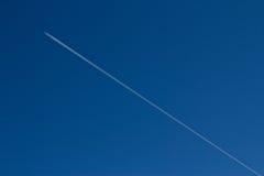 Contrail di un aeroplano e di un cielo blu immagine stock libera da diritti