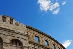 Contrail of the jet plane above ancient Roman amphitheater in Pula, Croatia Royalty Free Stock Photos