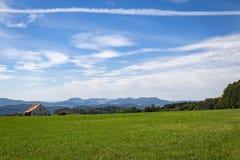 Contrail over blauwe hemel met bergen ver weg Stock Fotografie