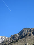Contrail vs Mountain. Contrail against bright blue sky crosses over craggy mountain ridge or peak royalty free stock photos