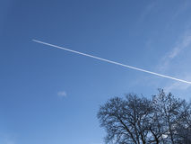 Contrail in winter sky Stock Photo