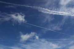 Contrails of air travel, sky with clouds and airpl Royalty Free Stock Photo