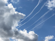 Contrails of aircraft and giants cumulonimbus clouds in the blue sky Stock Photo