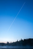 Contrails in the blue sky before sunrise Royalty Free Stock Photo