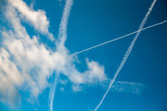 Contrails and clouds in blue sky. Contrails of jet planes and clouds in blue sky Royalty Free Stock Photography