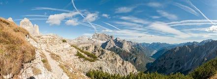 Contrails i himlen över berg Arkivbilder