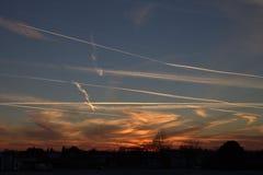 Contrails i himlen i aftonhimmelsolnedgången Arkivbild