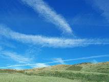 Contrails in the Marin Headlands, California. Airplanes create dramatic skies above the hills of the Marin Headlands Royalty Free Stock Photos
