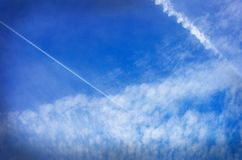Contrails och moln på härlig blå himmel royaltyfria foton