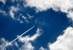 Contrails och strimlor av moln på härlig himmel arkivfoto
