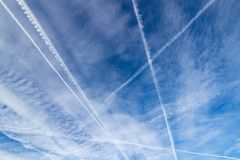 Contrails in the sky as geometric shapes triangle and crossing lines, converging lines stock photography