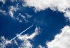 Contrails und Fetzen von Wolken am schönen Himmel stockfoto