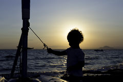 Contraluz de un niño en la playa Imagen de archivo