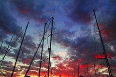 Contraluz dramático del cielo de la puesta del sol del mástil del barco de vela del puerto deportivo Imágenes de archivo libres de regalías